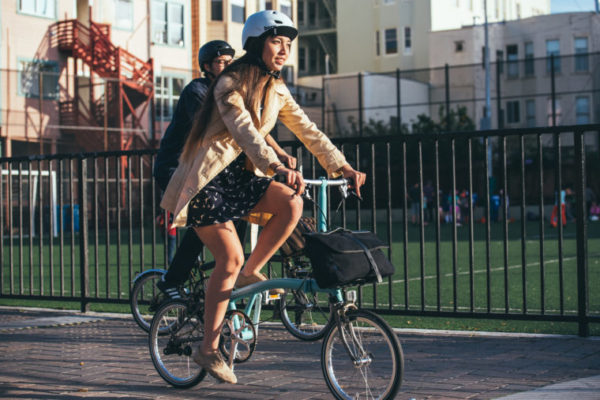 two people riding bikes near a park