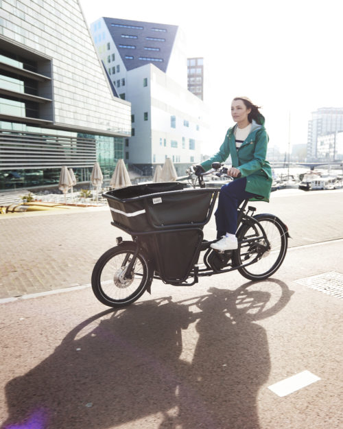 woman riding urban arrow bike through the city