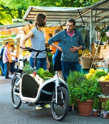 woman with a bike talking to a man in a market
