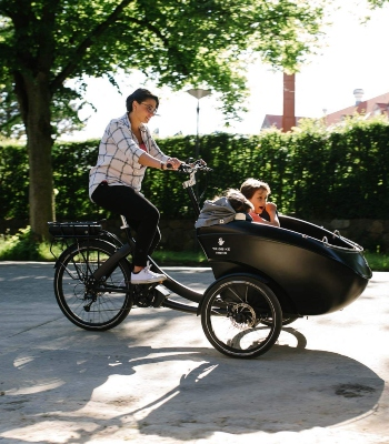 woman ridimg a bike with a box at the front where her daughter is sitting